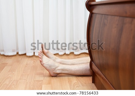 Bare hairy legs behind bed. Man lying on the floor in bedroom - stock photo