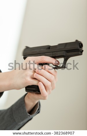 Bare Hands Holding a Firearm and Pointing Away From Camera, Ready to Shoot. - stock photo