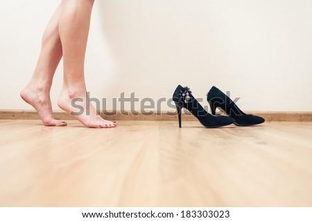 Bare legged women dancing near high heel shoes - stock photo