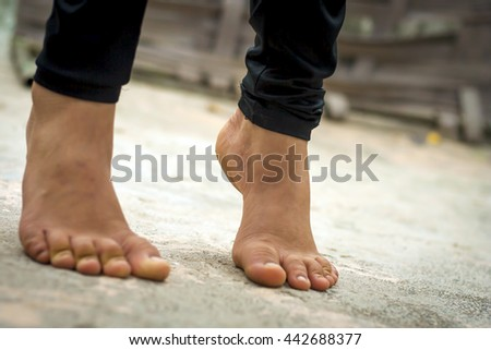 Barefoot Caucasian girl's legs, with heels up and on the rough surface. - stock photo