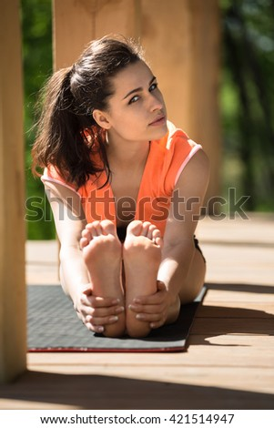 Barefoot girl is engaged in yoga on the wooden terrace on the nature background. She seated forward bend on the black yoga mat. She holds her feet with her hands. She looks into the camera with - stock photo