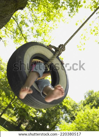 Barefoot girl on tire swing - stock photo