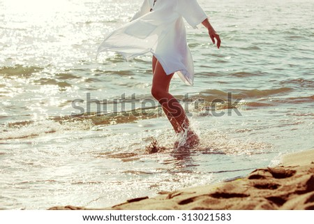 barefoot woman enjoy in sea water in white long shirt, lower body,  side view - stock photo