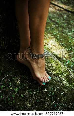 barefoot woman legs with anklet bracelets stand by tree in moss, natural light, selective focus - stock photo