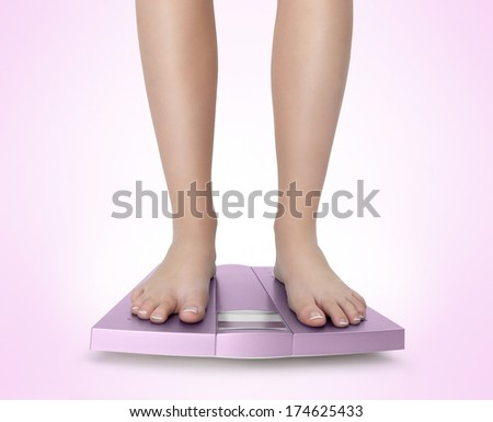 Barefoot woman on pink scale with balance diet - stock photo