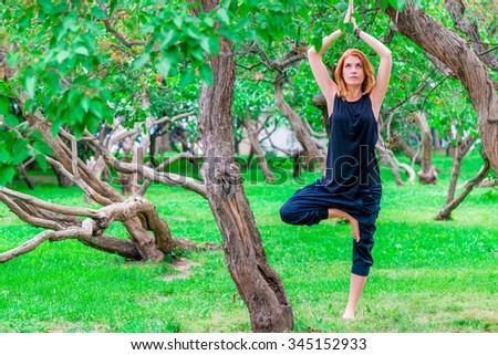 barefoot woman practices yoga in the park among the trees - stock photo