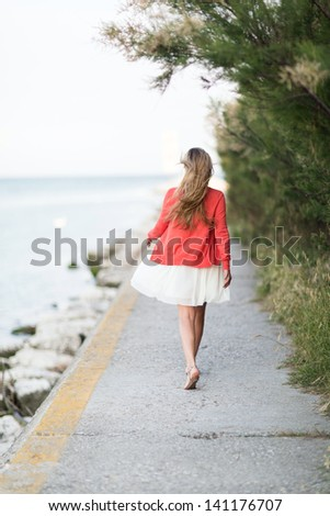 Barefoot woman taking a relaxing walk at the sea walking away from the camera along a walkway above the ocean - stock photo