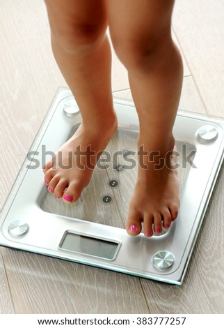 Barefoot woman with manicured toenails standing on a modern glass electronic bathroom scale as she checks her weight, close up high angle view of her legs - stock photo