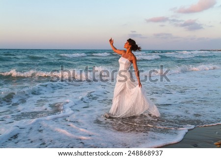 Barefoot young bride in a partially wet  wedding dress, enjoys walking in the water on a sandy beach in late summer, at dusk. - stock photo