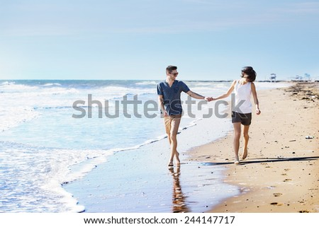 Barefoot young couple walking hand in hand along a beach at the edge of the surf as they spend a relaxing day at the seaside on their summer vacation - stock photo