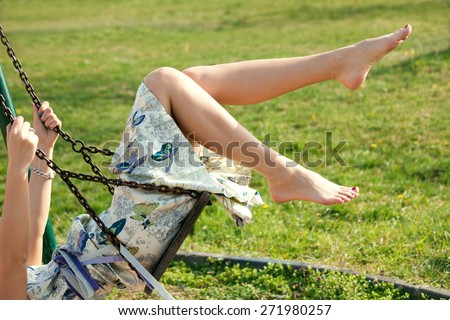 barefoot young woman in dress on swing outdoor in park warm spring day - stock photo