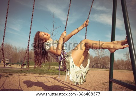 barefoot young woman sit on swing in summer dress  full body shot, retro colors - stock photo