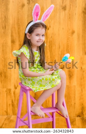 Barefooted little girl with long blond hair wearing pink white rabbit or bunny ears and holding bunch of colorful eggs sitting on pink chair. Easter celebrations. Wooden background. Studio portrait - stock photo