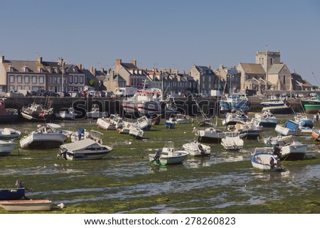 BARFLEUR, FRANCE - JULY 3, 2011: Fishing and recreational boats at low tide in the harbor of Barfleur. Barfleur is a picturesque fishing village in Basse Normandy. - stock photo