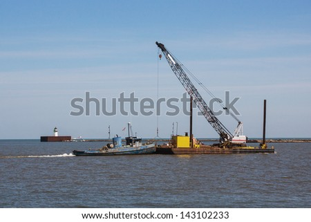 Barge And Crane:  A small tugboat pushes a construction crane sitting on a barge across the harbor at Cleveland, Ohio - stock photo
