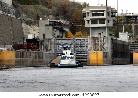 Barge loaded with gravel approaches the Lock and Dam No. 1 in Minneapolis - stock photo