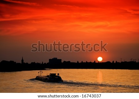 Barge with cargo at sunset - stock photo