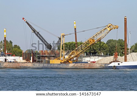 Barge with crane at construction site in Venetian Lagoon - stock photo