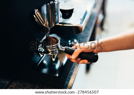 Barista grinding coffee for espresso - stock photo