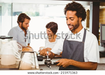 Barista grinding fresh coffee beans at the coffee shop - stock photo