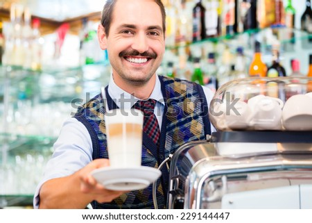 Barista in coffee bar offers latte macchiato in glass, in the background bottles  - stock photo