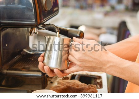 Barista mixing milk on espresso machine for making coffee, Latte and cappuccinoat the coffee machine at the coffee shop - stock photo
