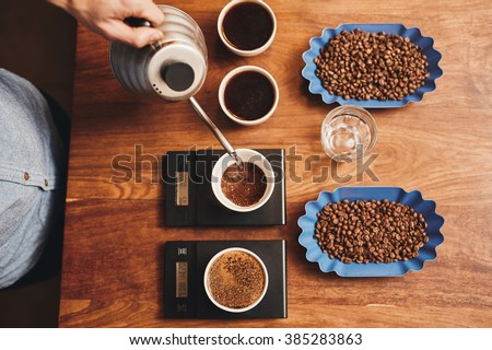Barista pouring water into cup of ground coffee on scale - stock photo