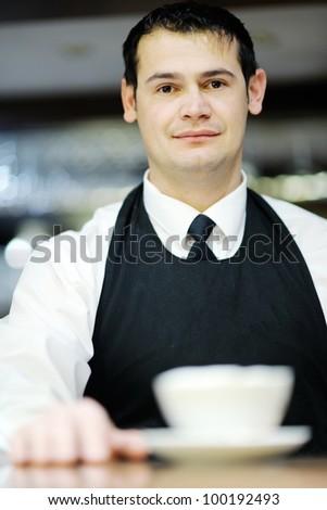 Barista prepares cappuccino in his coffee shop - stock photo