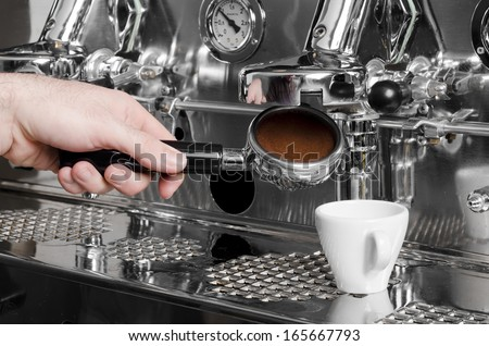 Barista prepares espresso in his coffee shop - stock photo