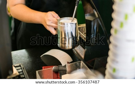 Barista Steaming Milk And Coffee In Coffeeshop - stock photo