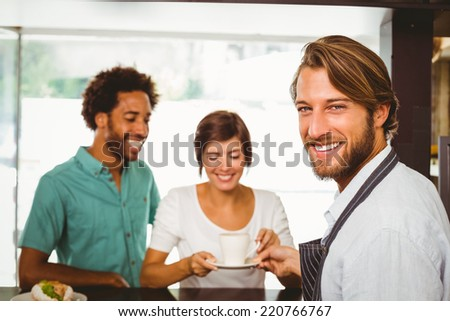 Barista talking with two customers at the coffee shop - stock photo