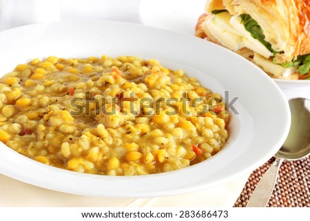 Barley and pea soup served with a brie and apple filled croissant, perfect meal for the vegetarian in your family - stock photo