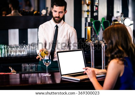 Barman giving a drink to customer using laptop in a bar - stock photo