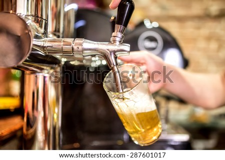 barman hand at beer tap pouring a draught lager beer serving in a restaurant or pub - stock photo