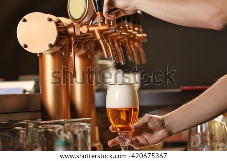 Barman hands pouring a lager beer in a glass. - stock photo