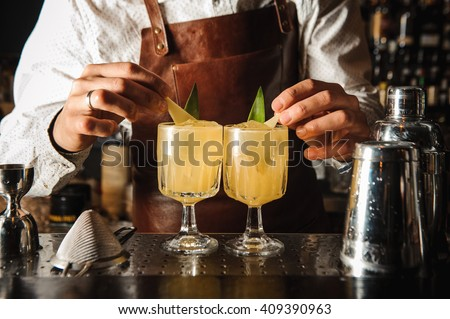 Barman is decorating cocktail with lemon no face - stock photo