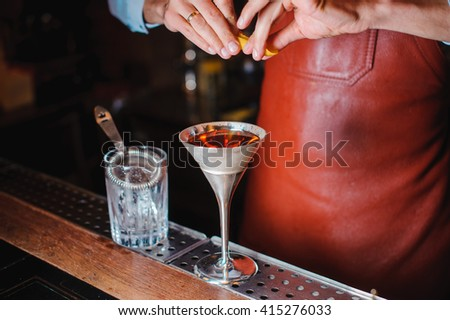 Barman is finishing up cocktail with lemon no face - stock photo