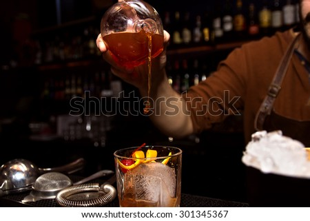 Barman is making cocktail at night club - stock photo