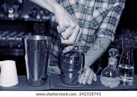 Barman is muddling cocktail ingredients in shaker, toned image - stock photo