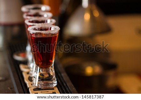 Barman make alcoholic shots in nightclub - stock photo