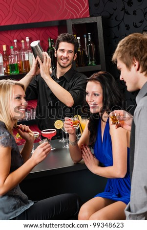 Barman making cocktail for young friends at the bar - stock photo