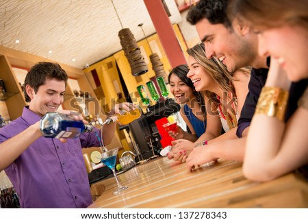 Barman making cocktails for a group of friends - stock photo