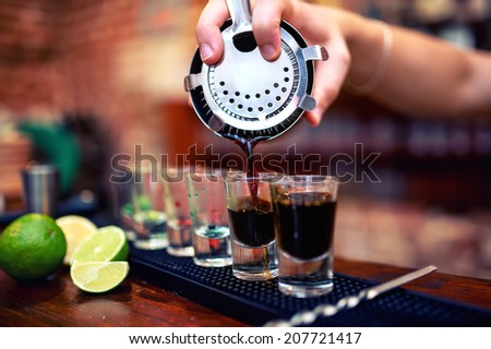 barman mixing and pouring a summer alcoholic cocktail into small, shot glasses on counter - stock photo