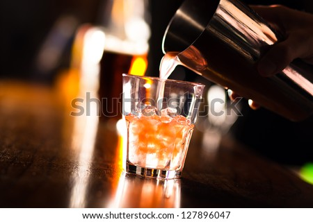 Barman pouring a cocktail into a glass - stock photo
