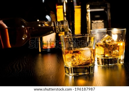 barman pouring whiskey in front of bottles on wood table, focus on top of bottle - stock photo