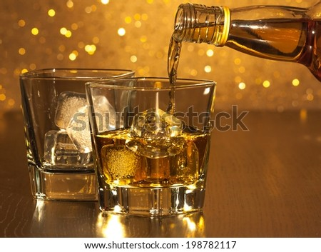 barman pouring whiskey in front of empty whiskey glass on gold bokeh - stock photo