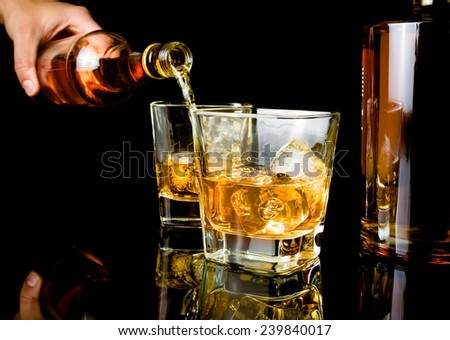 barman pouring whiskey in front of whiskey glass and bottles on black table with reflection - stock photo