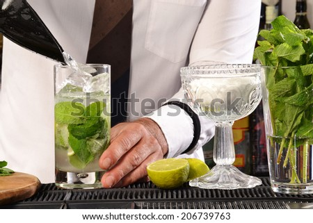 Barman preparing cocktail.Bartender preparing cocktail. - stock photo