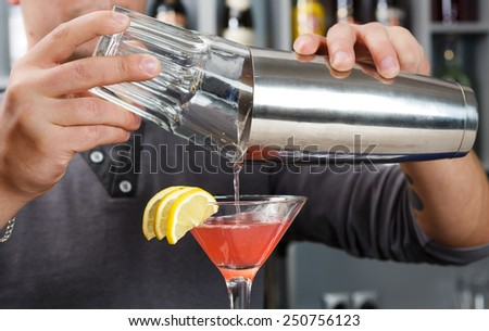 Barman's hands in bar interior mixing cosmopolitan cocktail - stock photo