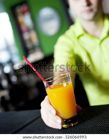 barman worker at bartender desk serving coctail in restaurant bar . focus on glass of juice - stock photo